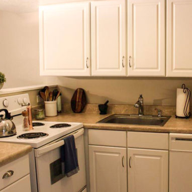 View of a kitchen with a white stove and stainless steel sink with white cabinets.